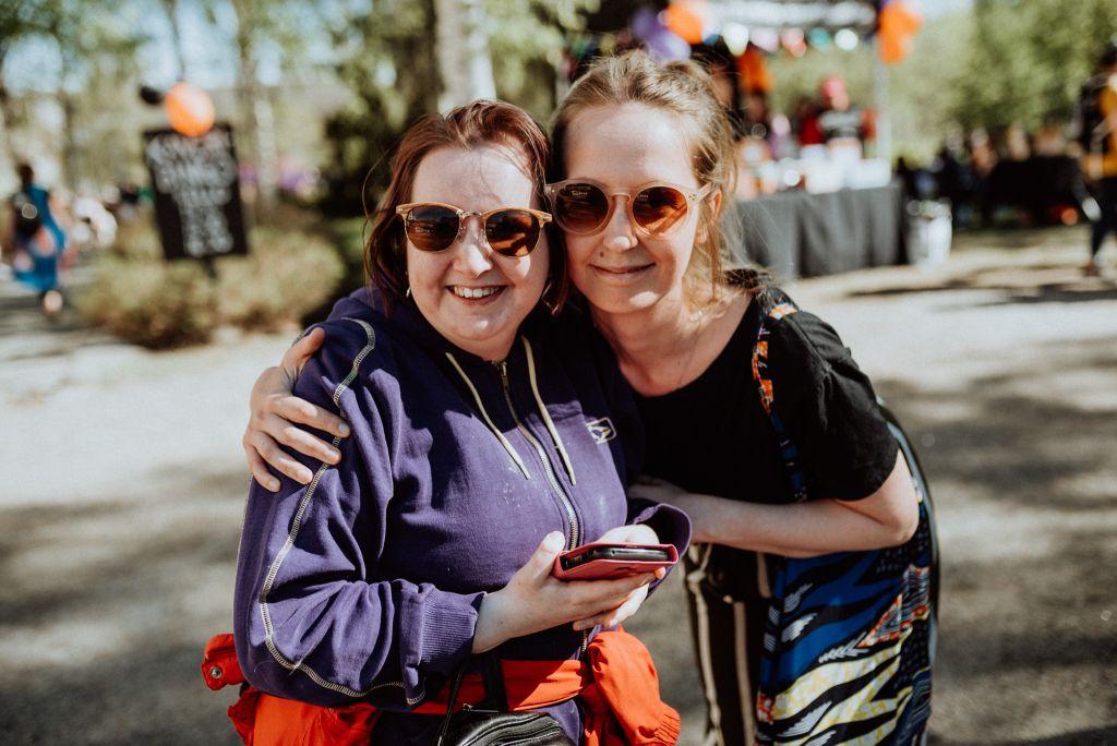Kaksi naista aurikolaiseissaan halaa, katsoo kameraan ja hymyilee.