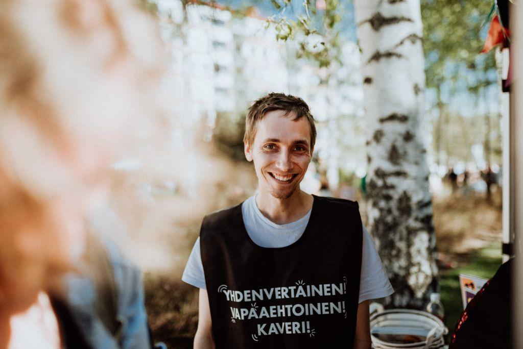 Mies hymyilee kameralle. Hänellä on yllään musta liivi, jossa lukee: yhdenvertainen, vapaaehtoinen, kaveri.