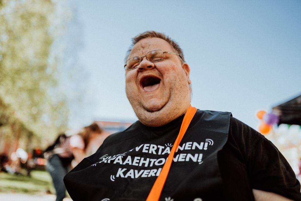 Hymyilevä mies, jolla yllään tunnisteliivi, jossa teksti: yhdenvertainen, vapaaehtoinen, kaveri.