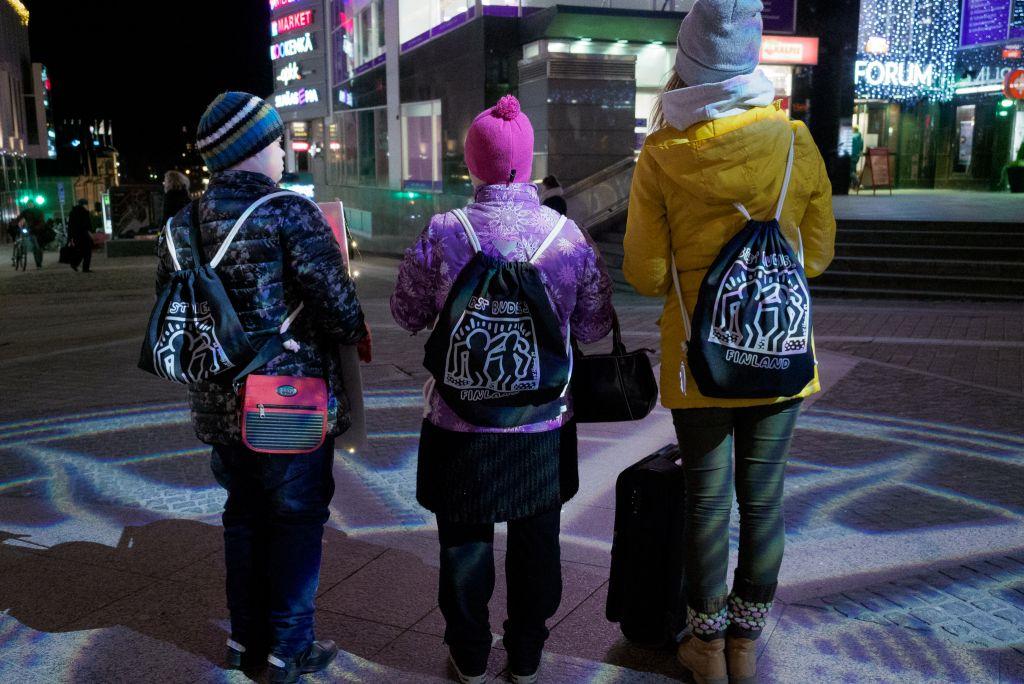 Kolme vapaaehtoista seisoo jouluisella kadulla selin kameraan.