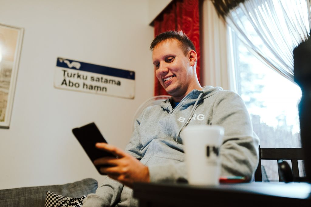 Mies hymyilee ja katsoo puhelintaan. Käynnissä on videopuhelu.