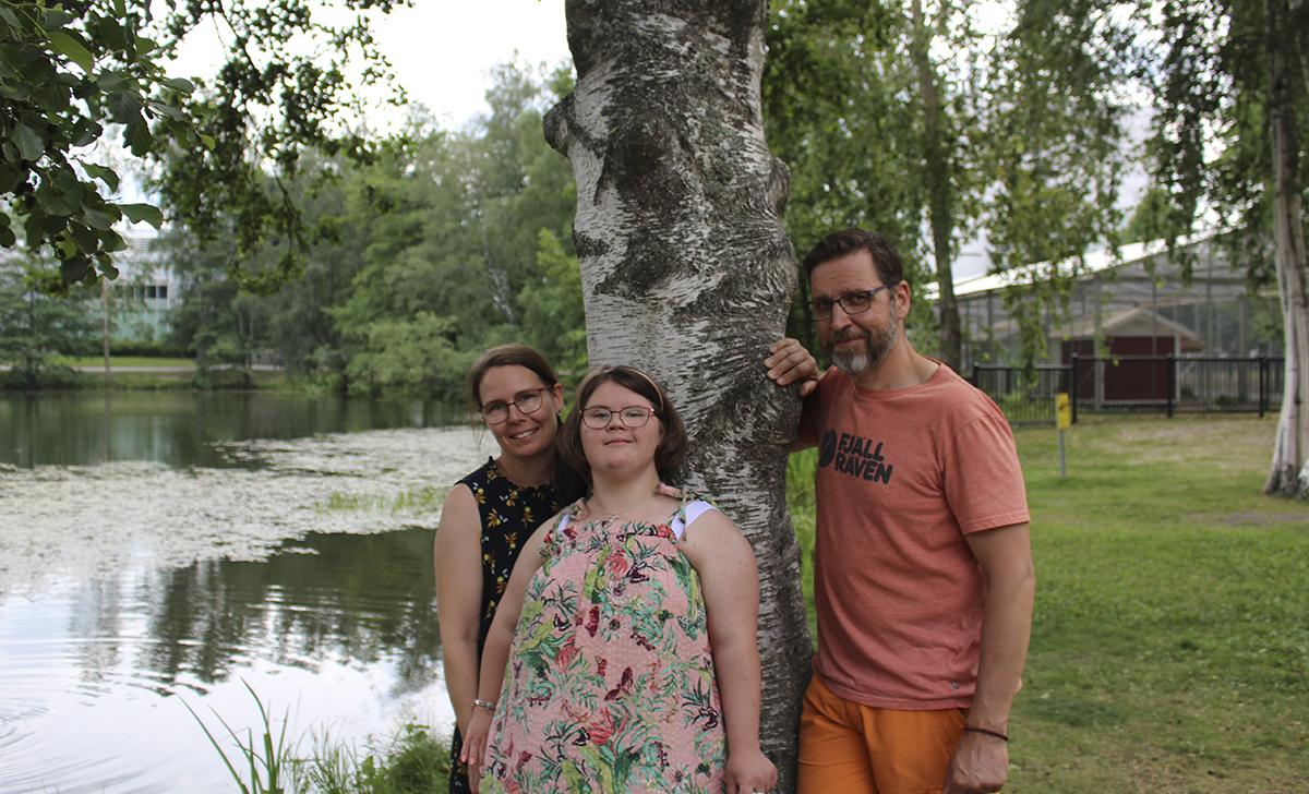 Taina, Silja ja Sami Nuottimäki seisovat kesäpäivänä Sorsapuistossa, rintama katsojaan päin nojaten koivuun.